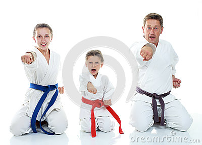 Dad with two daughters sitting in a ritual pose karate and beat his fist