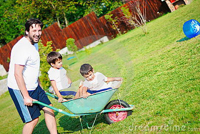 Dad in white driving his boys on the wheelbarrow