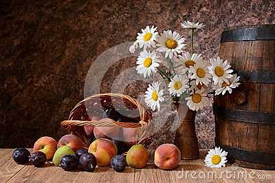 Daisy flowers in a vase with fresh fruits in a vicker basket