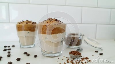 Dalgona coffee with ice, trendy korean drink on a white background, the brick wall  behind, dolly shot stock video