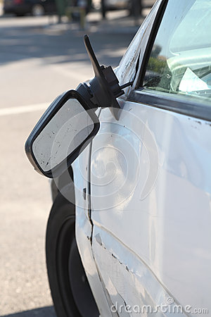 Damaged car and broken side rear view mirror.