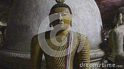 DAMBULLA, ШРИ-ЛАНКА - ФЕВРАЛЬ 2014: Закройте вверх по взгляду сидеть Buddhas на золотом виске Dambulla Золотой висок Dambu акции видеоматериалы