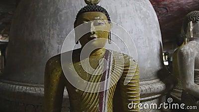 DAMBULLA, ШРИ-ЛАНКА - ФЕВРАЛЬ 2014: Закройте вверх по взгляду сидеть Buddhas на золотом виске Dambulla Золотой висок Dambu видеоматериал