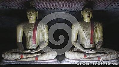 DAMBULLA, ШРИ-ЛАНКА - ФЕВРАЛЬ 2014: 2 сидя Buddhas на золотом виске Dambulla Золотой висок Dambulla Worl акции видеоматериалы