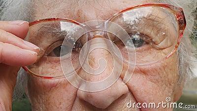 Dame âgée met dessus des verres et regarder la caméra Lunettes de port de mamie dehors Portrait de grand-mère triste extérieur banque de vidéos