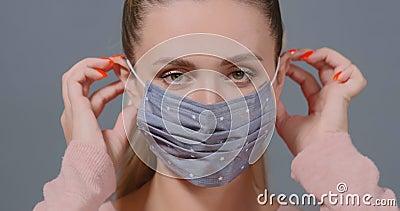Dame zet grijze polka dot beschermende medische maskers aan stock videobeelden