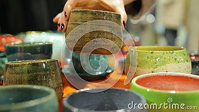 Damen som väljer dekorativ handgjord krukmakeri, bowlar på det keramiska lagret som shoppar arkivfilmer
