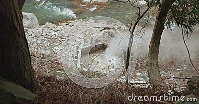 Dampf, der aus der geothermischen heißen Quelle ausströmt, wie ein Geysir neben einem Fluss in Japan stock video footage