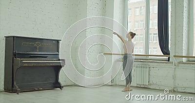 Dançarino de bailado clássico que exercita o plie do demi na barra video estoque