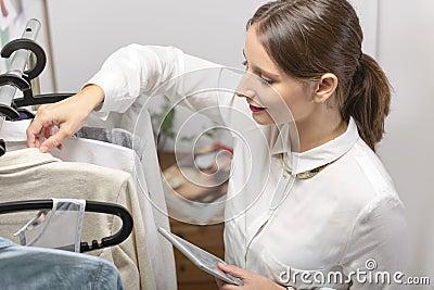 Dana kvinnan som väljer ett stycke för den nya samlingen med siffran