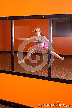 Dancer exercising in front of mirror