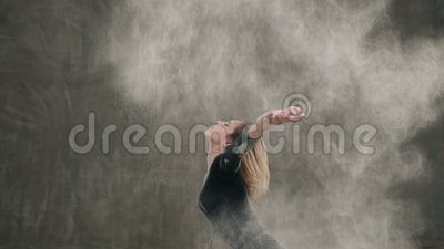 The dancer girl dressed in black body suit perform the contemporary dance on the floor, makes the stroke with the hair. Raising a cloud of dust or white powder stock video footage