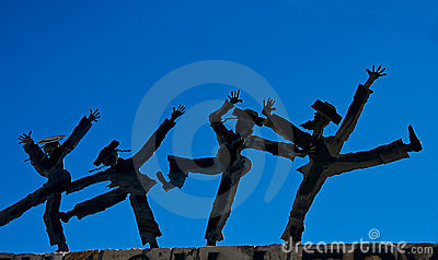 Dancing figurines against blue sky