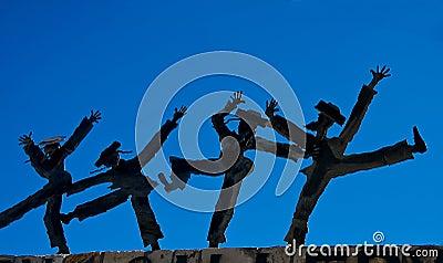 Dancing figurines against blue sky
