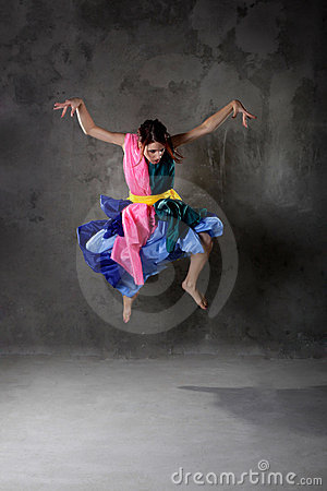 Dancing girl in colorful dress on the dirty grunge