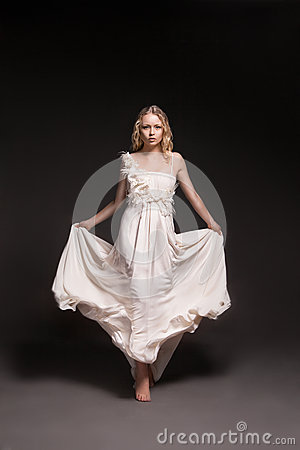 Dancing girl in wedding dress over dark background