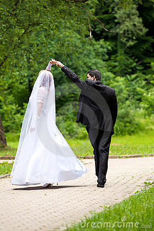 Dancing wedding couple at a park