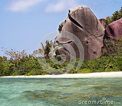 Dando boas-vindas à rocha na praia tropical do paraíso.