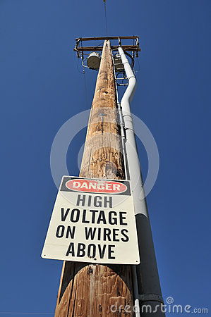 Danger high voltage wires above sign on pole