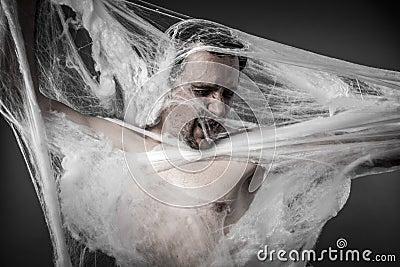 Danger. man tangled in huge white spider web