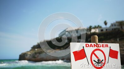 Danger, no swimming sign with red flags, blurred windy sea waves in background stock video