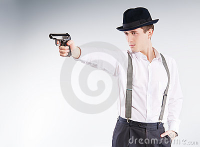 Dangerous gangster in hat aims a pistol