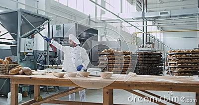 Dans une boulangerie grande vidéo d'un homme dansant boulanger écoutant de la musique depuis des écouteurs sans fil et jouant a banque de vidéos