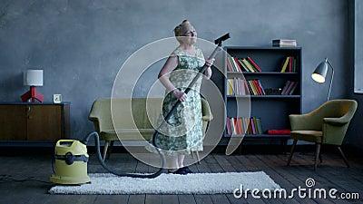 Danse heureuse de femme agée avec un aspirateur, amusement à la maison clips vidéos