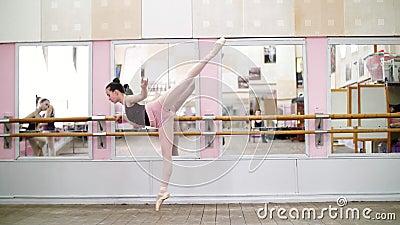 In dansende zaal, voert de Jonge ballerina in purpere maillot elegant een bepaalde balletoefening, arabesque in helling uit stock video