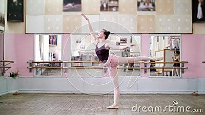 In dansende zaal, voert de Jonge ballerina in zwarte maillot 1 arabesque uit, opheft erachter haar been omhoog elegant, status stock video
