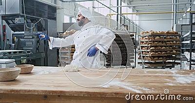Danser un charismatique boulanger à la barbe dans un uniforme élégant dans l'industrie de la grande boulangerie tout en écoutant  clips vidéos