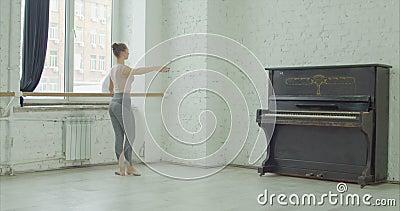 Danseur classique exerçant le tendu de battement au barre banque de vidéos
