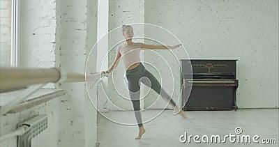 Danseuse de ballon exécutant un exercice passe-partout à la barre banque de vidéos