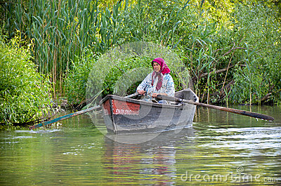 Danube delta - water city: old woman floating a boat Editorial Photo