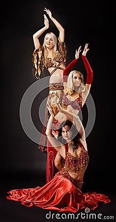 Danza de la mujer joven tres en traje árabe