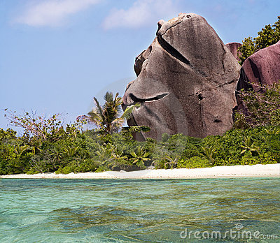 Dar la bienvenida a la roca en la playa tropical del paraíso.