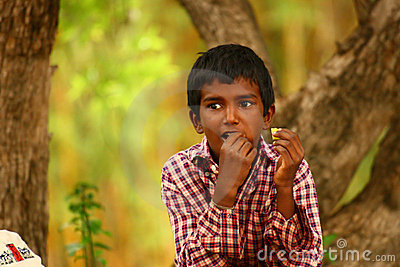 Dark Boy with finger in mouth eating food Editorial Image
