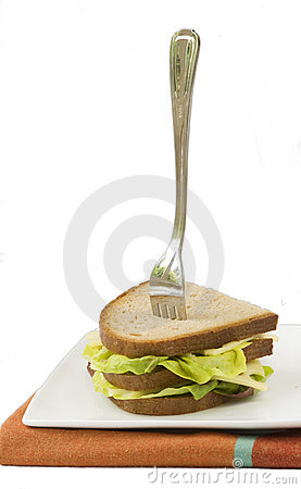 Dark bread sandwich with standing fork, isolated