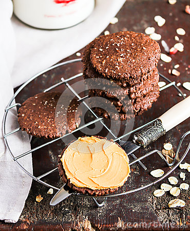 Free Dark Chocolate Sandwich Cookies With Oat Flakes And Peanut Butter Cream Stacked On A Cooling Rack On A Wooden Table Stock Image - 90309031