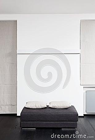 Dark gray padded stool with white pillow