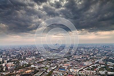 Dark grey autumn clouds under big city