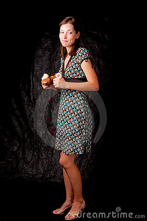 Dark haired girl standing colored dress on black