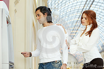 Dark-haired man with credit card and red-haired woman stand