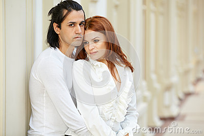 Dark-haired man and red-haired woman stand embraced