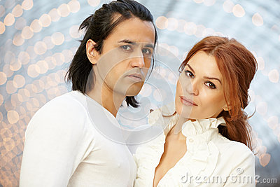 Dark-haired man and red-haired woman stand side by side
