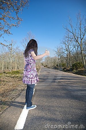 Dark-haired woman hitchhiking