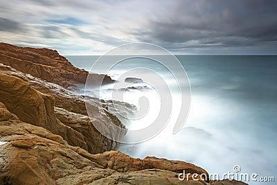Dark red rocks, foam and waves, sea under bad weather.