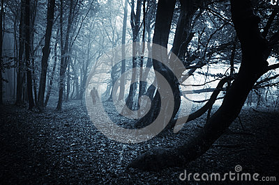 Dark scene of a spooky man walking in a dark forest with blue fog