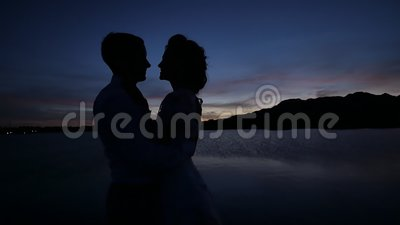 Dark silhouettes of the bride and groom on a tropical ocean beach at sunset. Sensual hugs and kisses. Dark silhouettes of the bride and groom on a tropical stock video footage