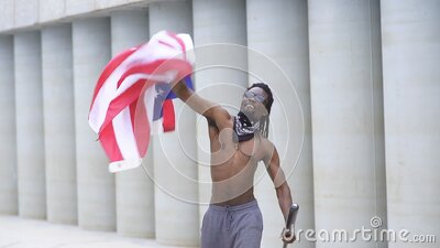 Dark-skinned protester with a bat in hands waves an American flag and throws it into the air stock video